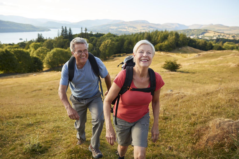 Mann und Frau über 50 wandern in der Nähe eines Sees