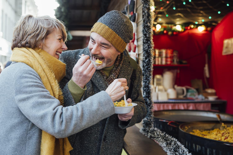 Glücklicher Mann und lachende Frau über 50 essen Paella auf dem Weihnachtsmarkt